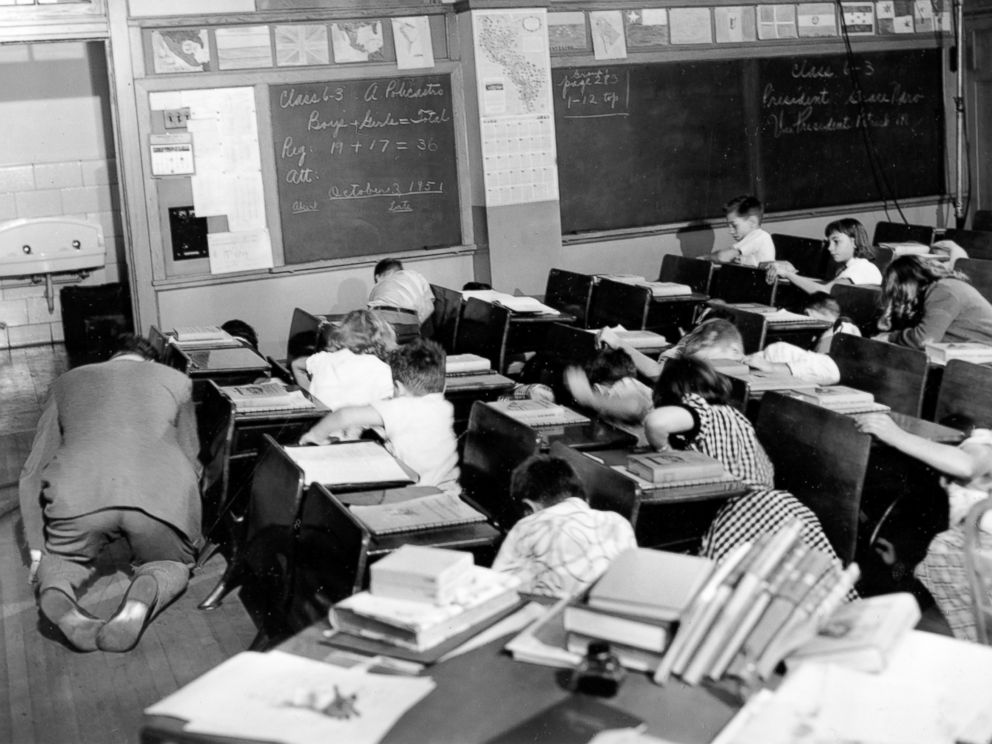PHOTO: Sixth grade students crouch under or beside their desks along with their teacher as they act out a scene from the Federal Civil Defense administration film Duck and Cover in the Queens, Nov. 21, 1951.