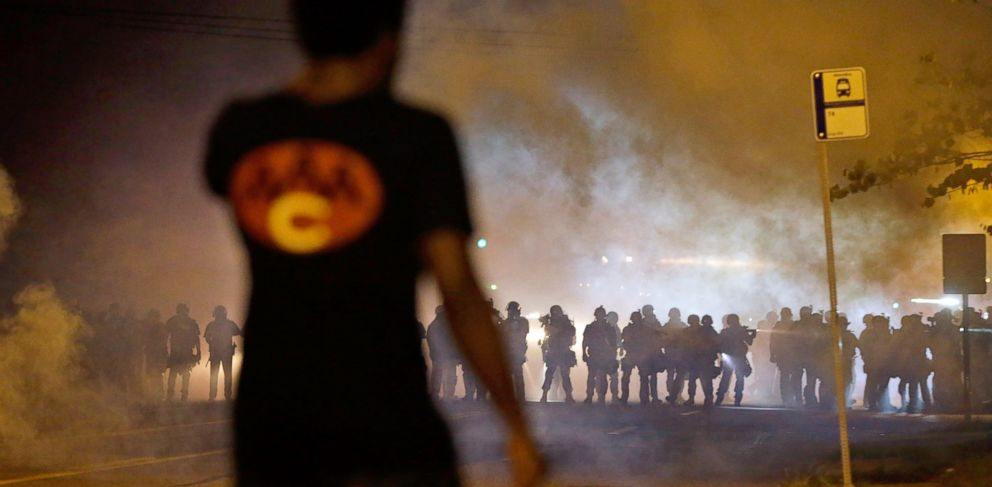 PHOTO: A man watches as police walk through a cloud of smoke during a clash with protesters in Ferguson, Mo., Aug. 13, 2014.