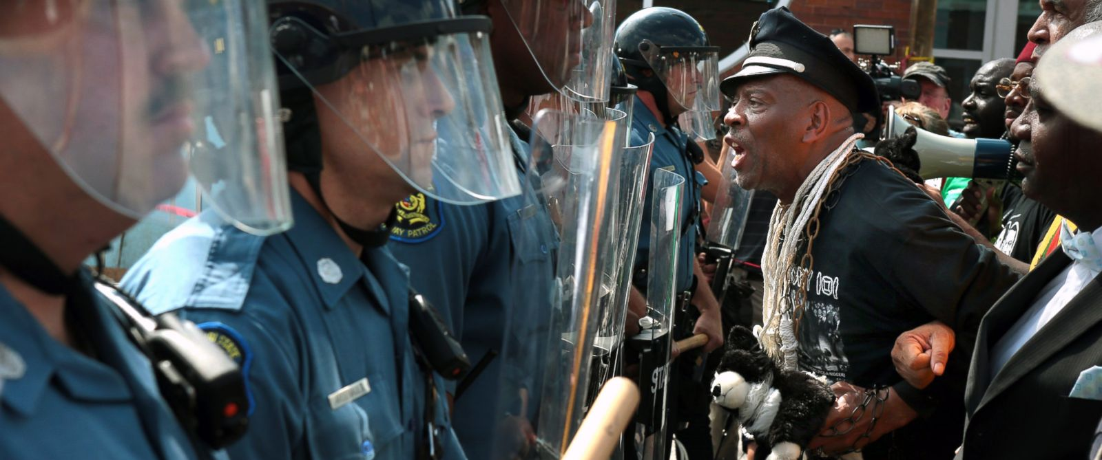 PHOTO: Protester Anthony Shahid leads marchers as they confront Missouri State Highway Patrol trooper in front of the Ferguson police station, Aug. 11, 2014, in Ferguson, Mo.