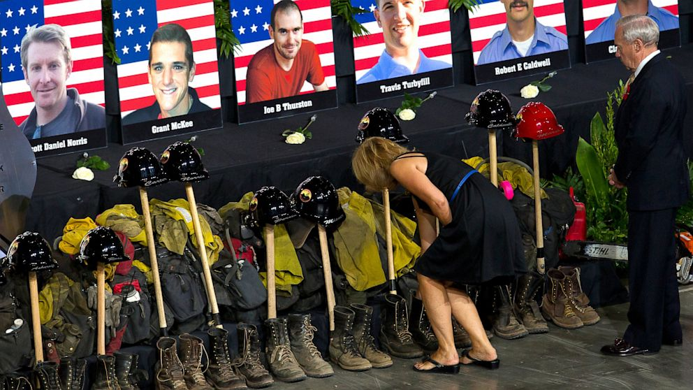 PHOTO: 19 fallen firefighters line the front of the stage before a memorial service