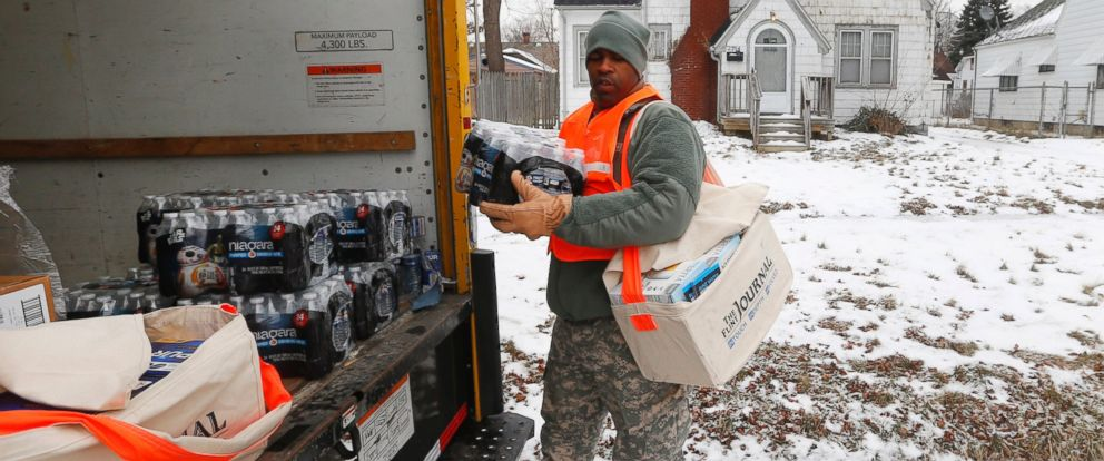 PHOTO: Michigan National Guard Specialist Lonnie Walker unloads bottled water and filters to distribute to residents, Jan. 21, 2016, in Flint, Mich.