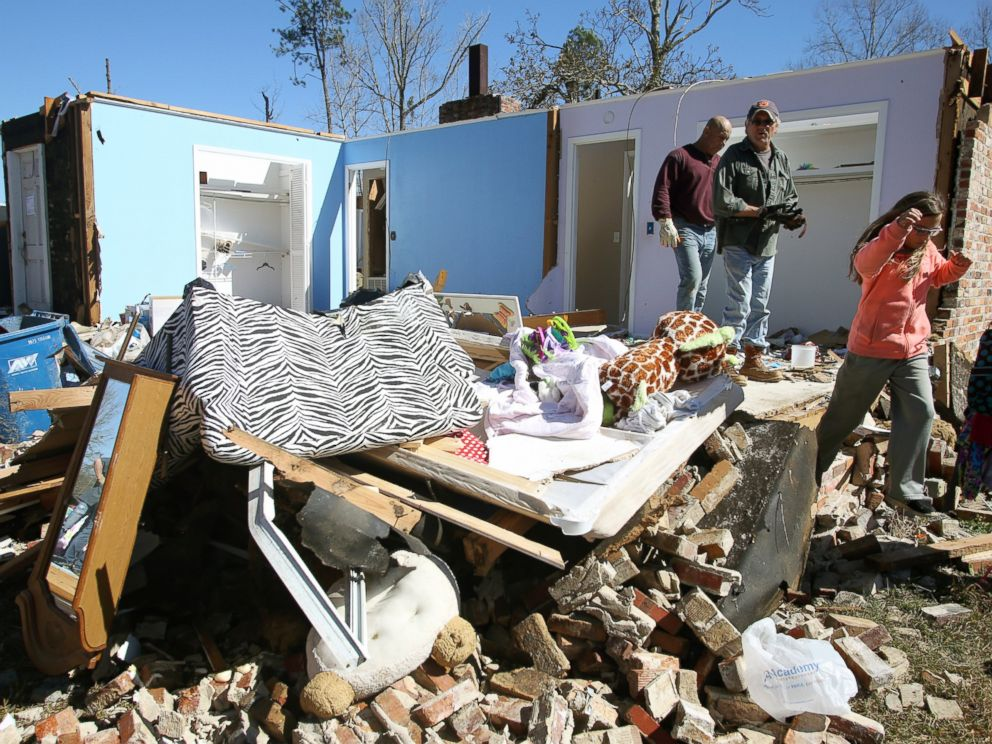 PHOTO: Residents and neighbors salvage items from the debris of a home that was damaged by severe weather that struck the prior evening in Century, Fla., Feb. 16, 2016.