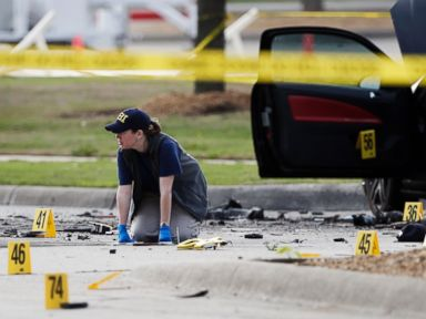 PHOTO: An FBI crime scene investigator documents the area around two deceased gunmen and their vehicle outside the Curtis Culwell Center in Garland, Texas, May 4, 2015.