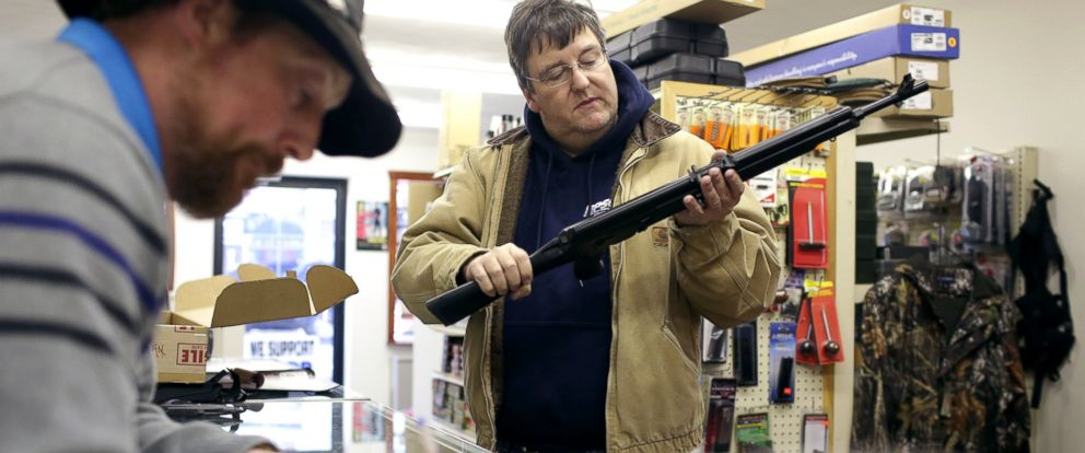 PHOTO: Joe McGrew, of Lake Ariel, Pa., inspects his new Saiga AK-47 style rifle as Rich Johnson, left, owner of Big Rich American Sports Shop, processes his background check in Scranton, Pa., Jan. 5, 2016.