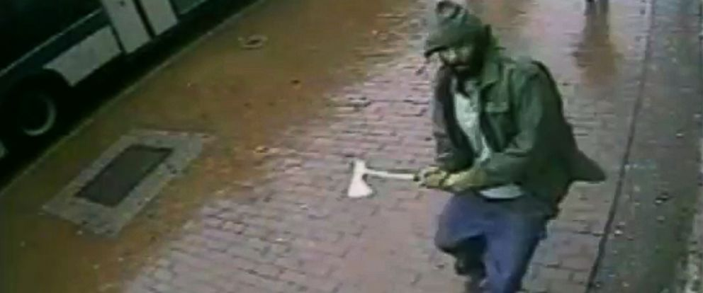 PHOTO: In a frame grab taken from surveillance video by the New York City Police Department, an unidentified man approaches New York City police officers with a hatchet in the citys Queens borough, Oct. 23, 2014.