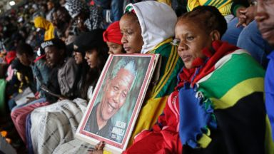PHOTO: People huddle under blankets during the memorial service for former South African president Nelson Mandela at the FNB Stadium in Soweto, near Johannesburg, South Africa, Dec. 10, 2013.