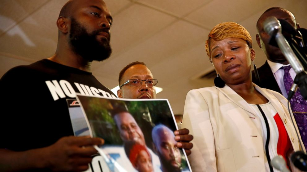 PHOTO: Lesley McSpadden, right, the mother of 18-year-old Michael Brown, watches as Browns father, Michael Brown Sr., holds up a family picture of himself, his son, top left in photo, and a young child during a news conference.