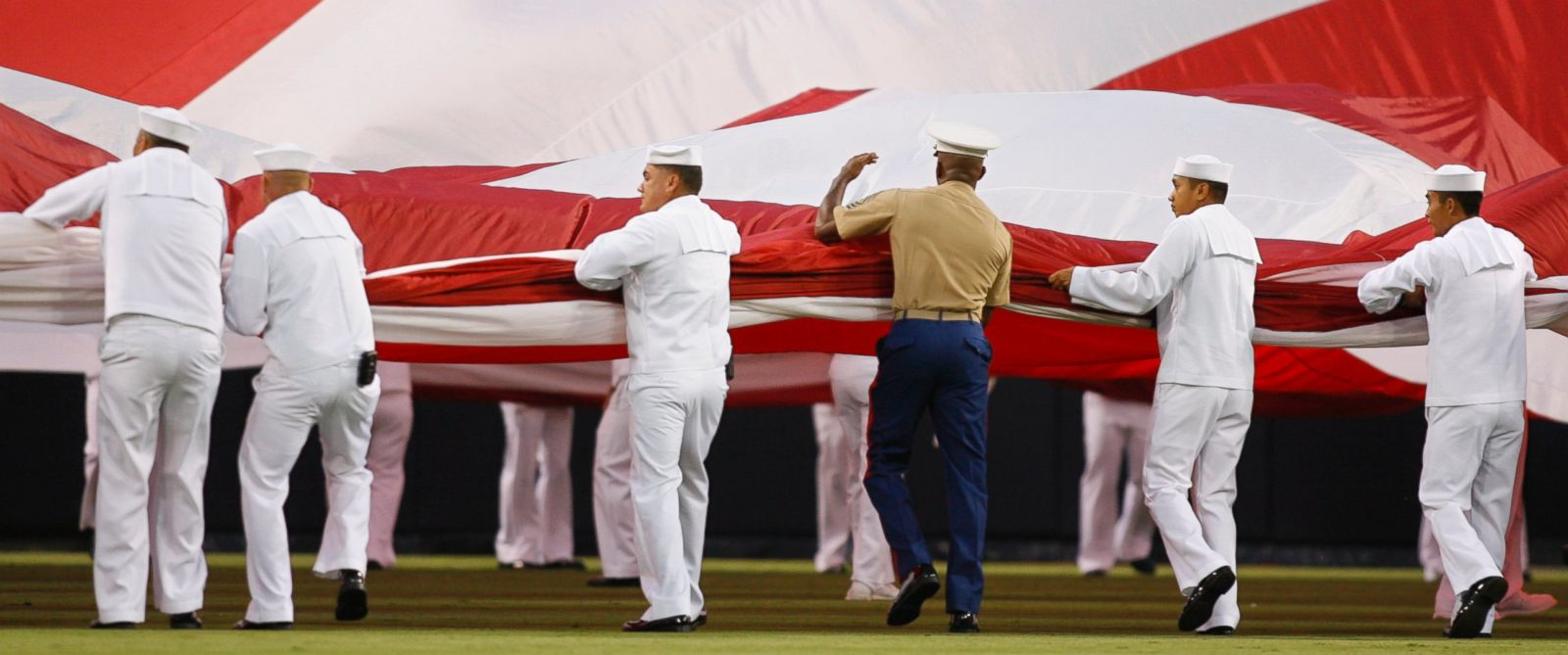 PHOTO U.S. military service members unfurl an American flag during a ceremony held to commemorate the anniversary of the 9/11 attacks before a baseball game between the the San Diego Padres and the Colorado Rockies Friday, Sept. 11, 2009 in San Diego.