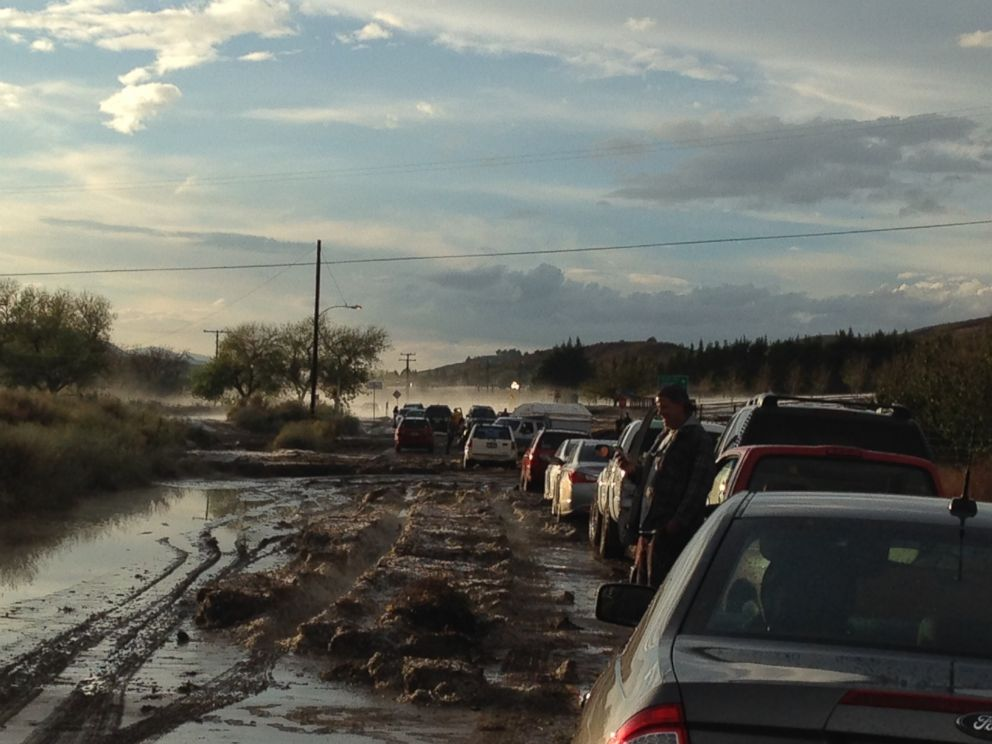 PHOTO: Cars on a road are stopped because of flooding, with some stuck in the mud in the distance, in Lake Hughes, Calif, Oct. 15, 2015.