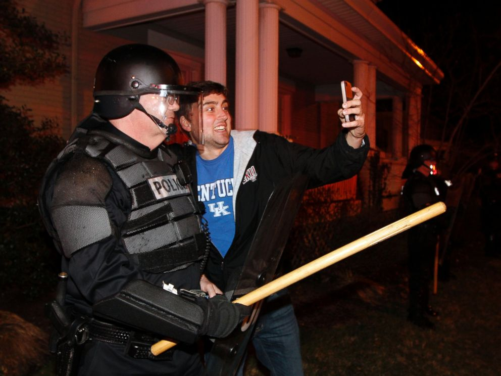 PHOTO: Eastern Kentucky University junior Eric Kuertz, right, takes a selfie with UK Police officer Lt. Greg Hall as Kentucky fans react to their teams semi-final victory on State St., Saturday, April 5, 2014, in Lexington, Ky.