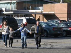 PHOTO: A police officer leads two women and a child from Sandy Hook Elementary School