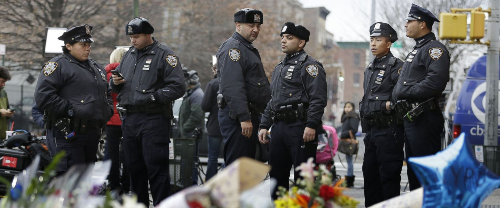 PHOTO: New York City police officers gather near a makeshift memorial near the site where fellow officers Rafael Ramos and Wenjian Liu were murdered in the Brooklyn borough of New York, Dec. 22, 2014.