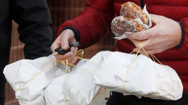 PHOTO: A customer leaves a popular sweet shop in Warsaw, Poland with packets full of fresh jam-filled doughnuts, or Paczki, on Fat Thursday in Warsaw, Poland, Feb. 27, 2014.
