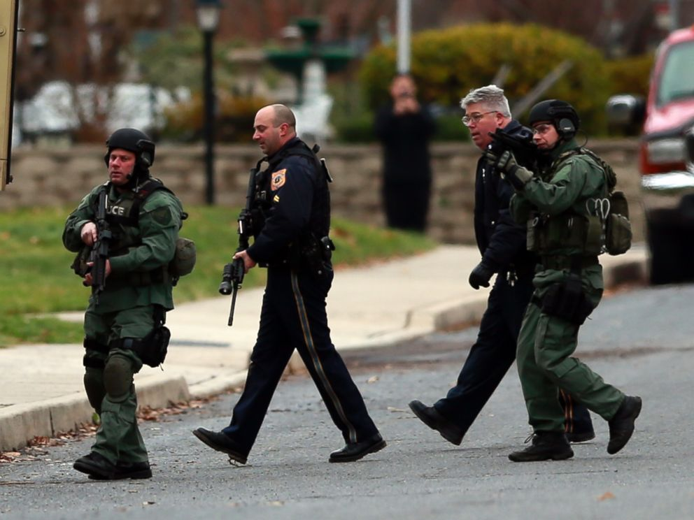 PHOTO: Police move near a home where a suspect is believed to have barricaded himself inside