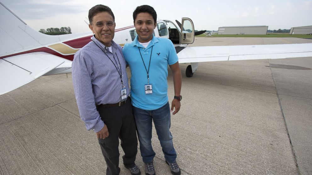PHOTO: In this June 19, 2014 photo, Babar Suleman and son Haris Suleman, 17, stand next to their plane at an airport in Greenwood, Ind. before taking off for an around-the-world flight.