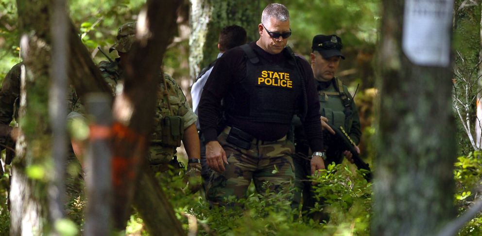 PHOTO: A Pennsylvania State Trooper and others investigate a wooded area across from the police barracks, Sept. 14, 2014, in Blooming Grove Township, Pa.