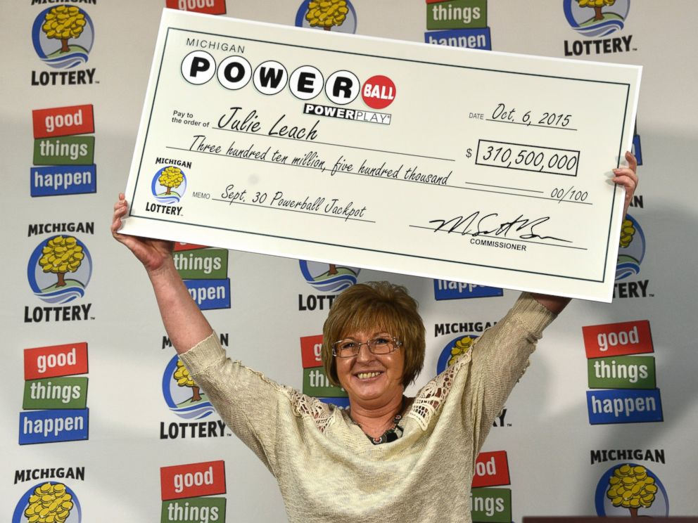 PHOTO: Julie Leach holds her $310 Million check aloft on Oct. 6, 2015. She was the sole winner of the Powerball jackpot.