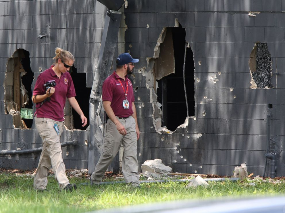 PHOTO: Investigators from the office of the medical examiner investigate on the west side of Pulse nightclub where a gunman opened fire on Sunday morning, June 12, 2016, in Orlando, Fla.