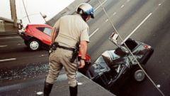 PHOTO: In this photo taken Oct. 17, 1989, a California Highway Patrol Officer checks the damage to cars that fell when the upper deck of the Bay Bridge collapsed onto the lower deck after the Loma Prieta earthquake in San Francisco.