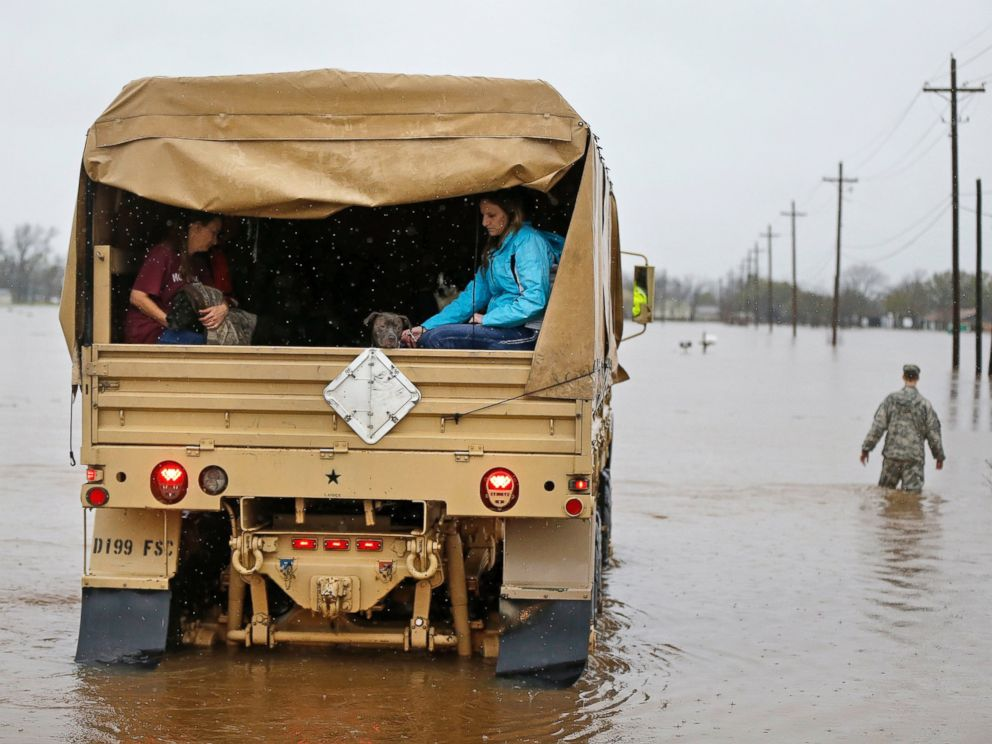 PHOTO: People sit in the back of a Louisiana National Guard truck as they are evacuated from rising floodwaters in Bossier Parish, La., March 10, 2016.