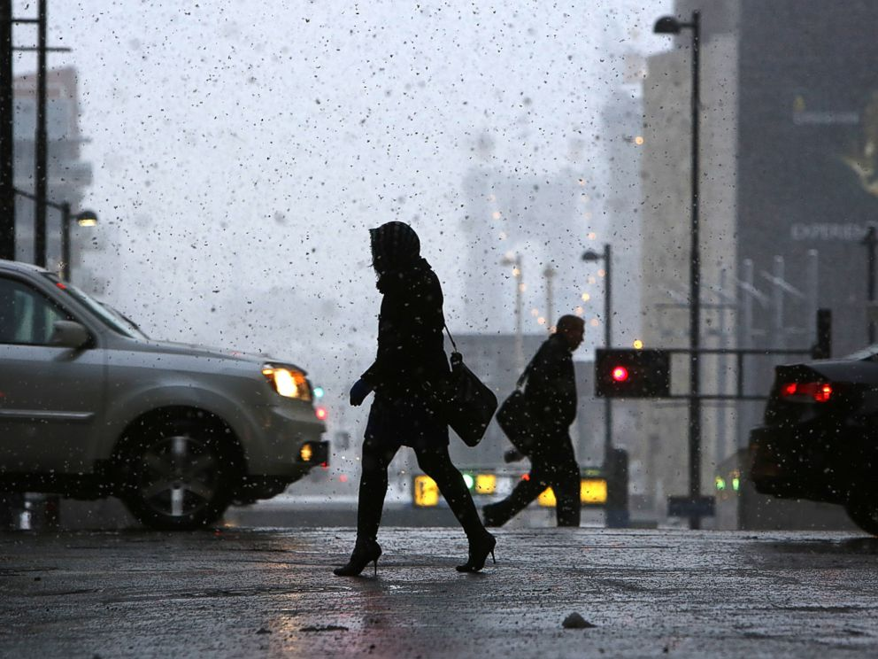 PHOTO:: Pedestrians make their way through downtown Cincinnati, Nov. 17, 2014, as the seasons first snowfall resulted in thousands of power outages in the Cincinnati area.