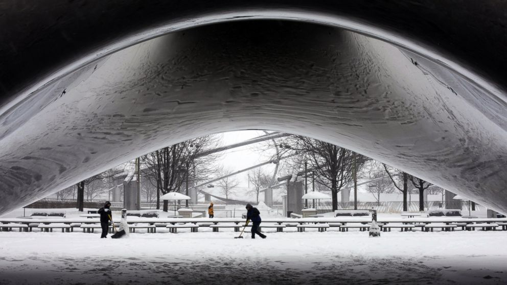 PHOTO: A park crew clears the snow around Annish Kapoors stainless steel Cloud Gate sculpture at Millennium Park, Jan. 2, 2014, as snow continues to accumulate in downtown Chicago.