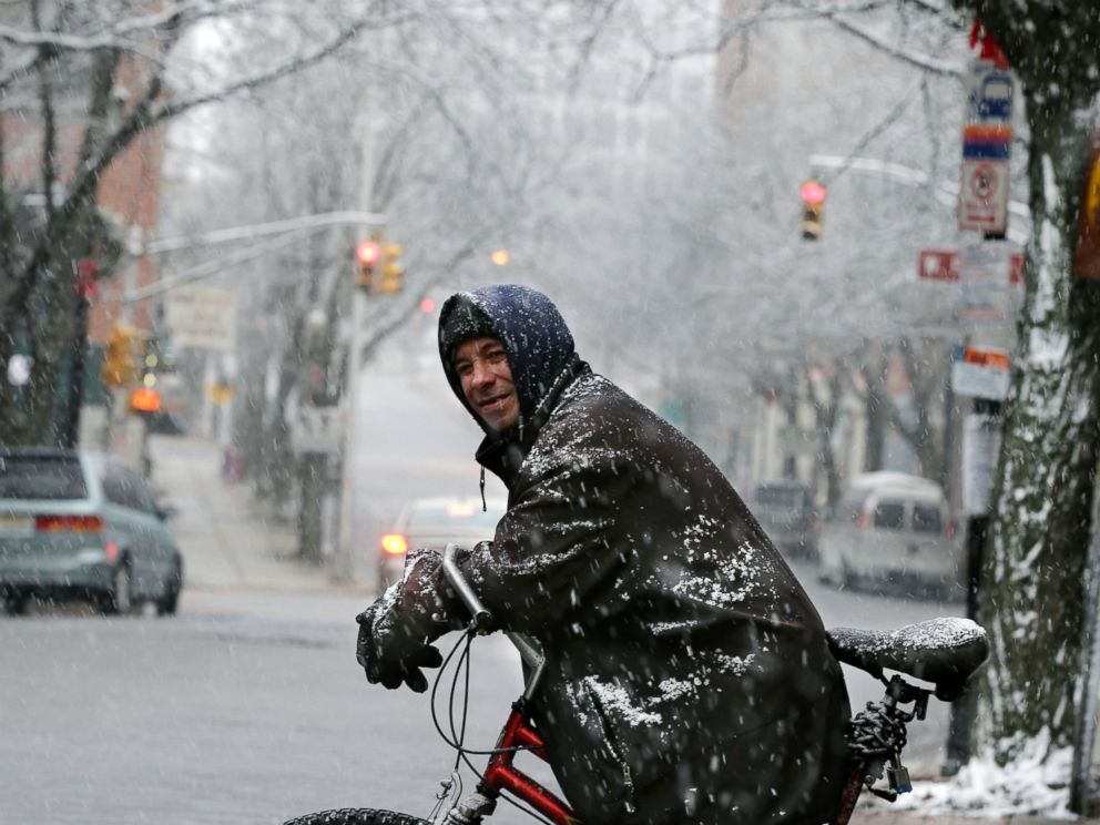 PHOTO: Rob Bitz rests on his bicycle in the snow along a street on Jan. 17, 2016, in Trenton, N.J.