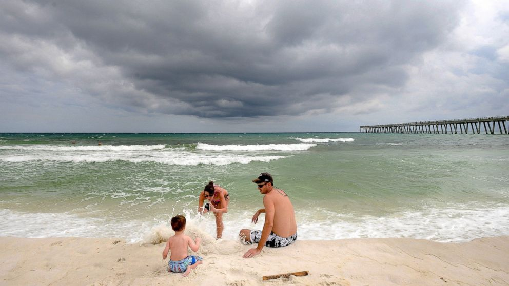 PHOTO: Deanna Smith of Cordele, Ga., takes a photo of her husband, Josh, and their son Noah, 2, on Navarre Beach in Navarre, Fla., as a storm moved into the area, Aug. 29, 2014.