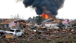 PHOTO: A fire burns in the Tower Plaza Addition in Moore, Okla., following a tornado, May 20, 2013.