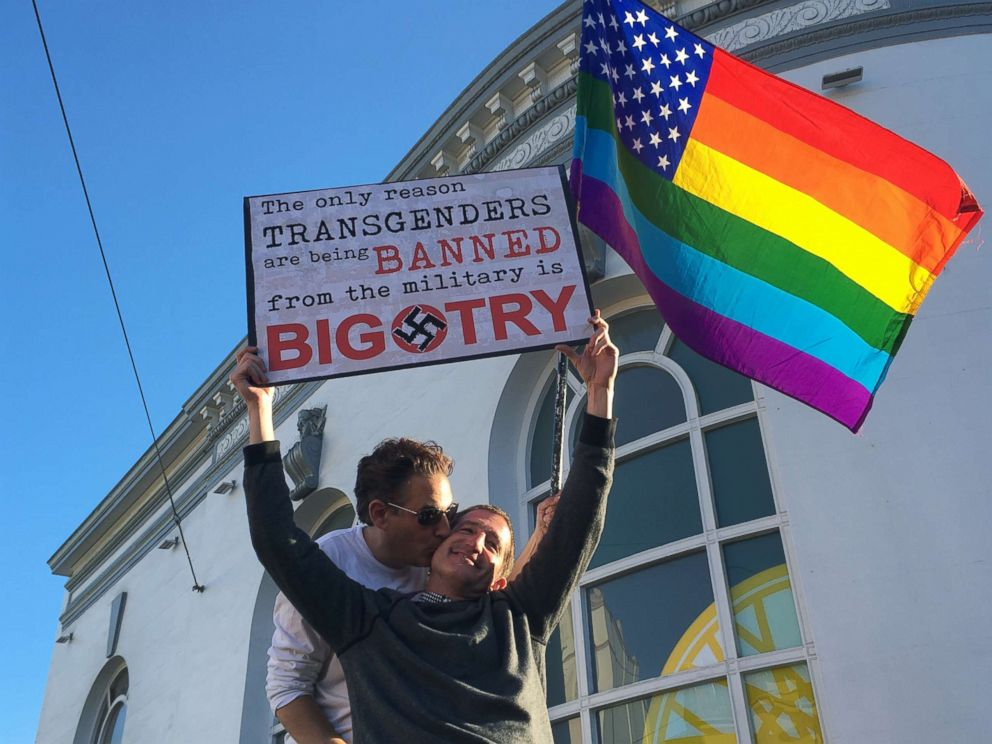 PHOTO: Nick Rondoletto, left, and Doug Thorogood, a couple from San Francisco, wave a rainbow flag and hold a sign against a proposed ban of transgendered people in the military at a protest in the Castro District.