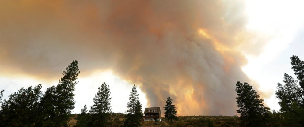 PHOTO: Smoke from an approaching wildfire looms over a home near Twisp, Wash., Wednesday, Aug. 19, 2015. Authorities on Wednesday afternoon urged people in the north-central Washington town to evacuate because of a fast-moving wildfire.
