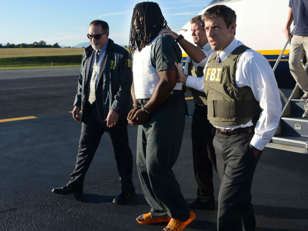 In this Friday, Sept. 26, 2014 photo provided by the FBI, agents escort Jesse Leroy Matthew, Jr., center, from a plane during extradition to Charlottesville, Va.