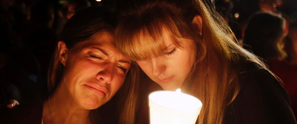 PHOTO: Kristen Sterner, left, and Carrissa Welding, both students at Umpqua Community College, embrace each other during a candlelight vigil for those killed during a shooting at the college, Oct. 1, 2015, in Roseburg, Ore.