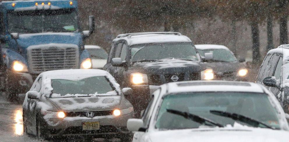 PHOTO: Vehicles cruise under light snowfall on Nov. 26, 2014, in Newark, N.J.