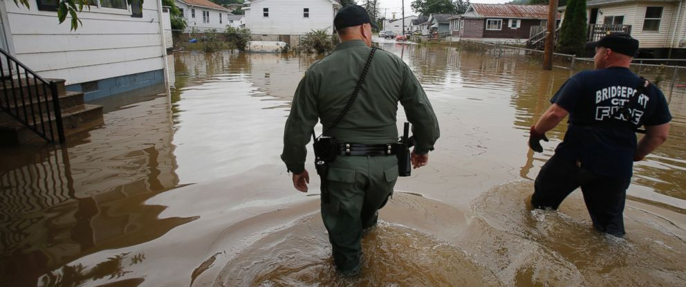 PHOTO: West Virginia State Trooper C.S. Hartman, left, and Bridgeport W.Va. fireman, Ryan Moran, wade through flooded streets as they search homes in Rainelle, W. Va., June 25, 2016.
