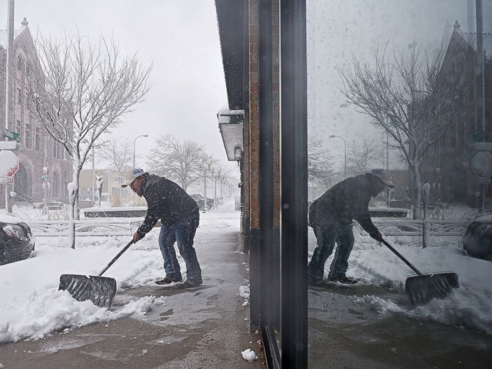 PHOTO: Philip Peter shovels snow in front of the restaurant during a snow storm, Nov. 18, 2016, in Sioux Falls, South Dakota.