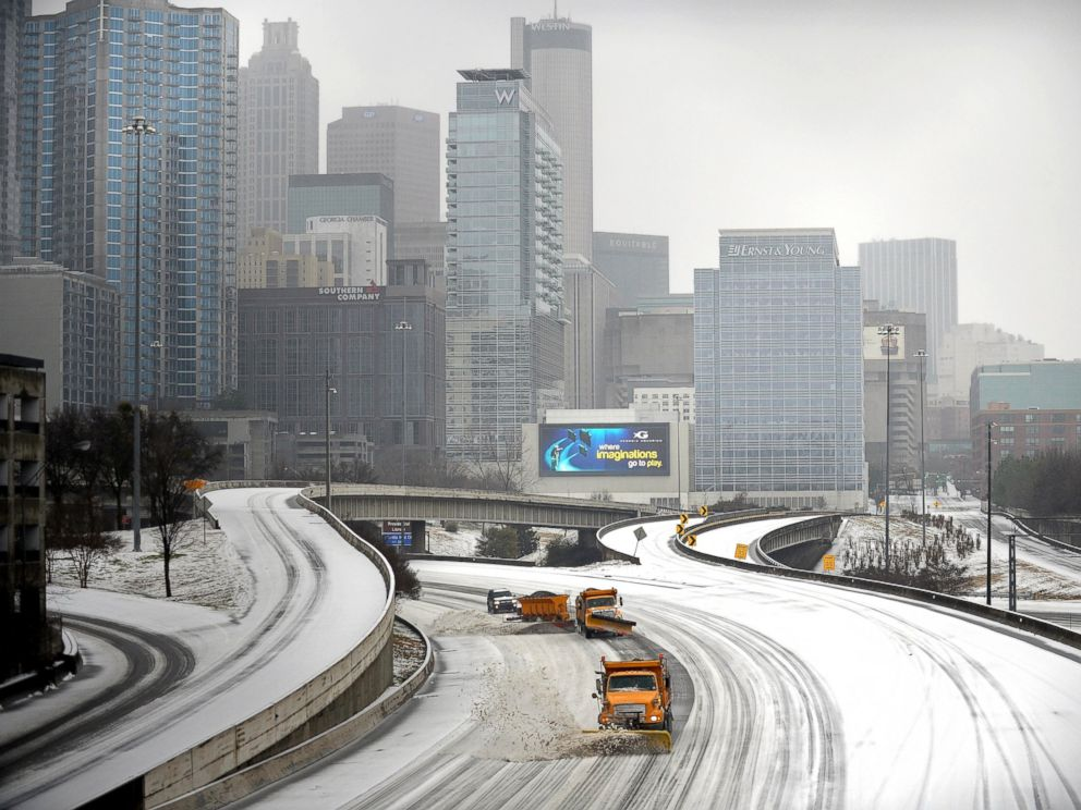 PHOTO: Snow plows clear Interstate 75/85 on the downtown connector while transportation and business grinds to a halt during a winter storm, Feb. 12, 2014, in Atlanta.