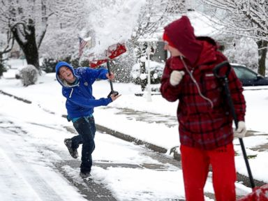 PHOTO: Austin Peters and Codi Consentino of Phillipsburg,N.J. play in the snow as they walk up John Mitchell Avenue, Dec. 10, 2013.