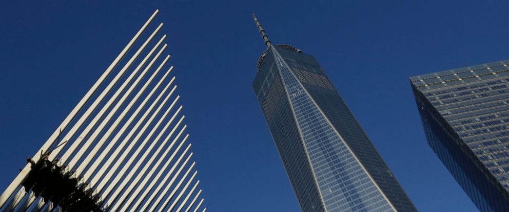 PHOTO: One World Trade Center stands between the transportation hub, left, still under construction, and 7 World Trade Center, right, Nov. 3, 2014 in New York.