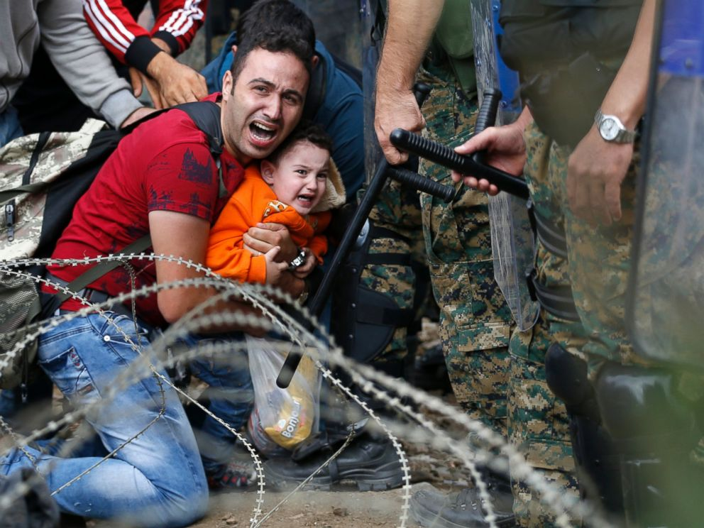 PHOTO:A refugee holding a boy react as they are stuck between Macedonian riot police officers and refugees during a clash near the border train station of Idomeni, northern Greece, Aug. 21, 2015.