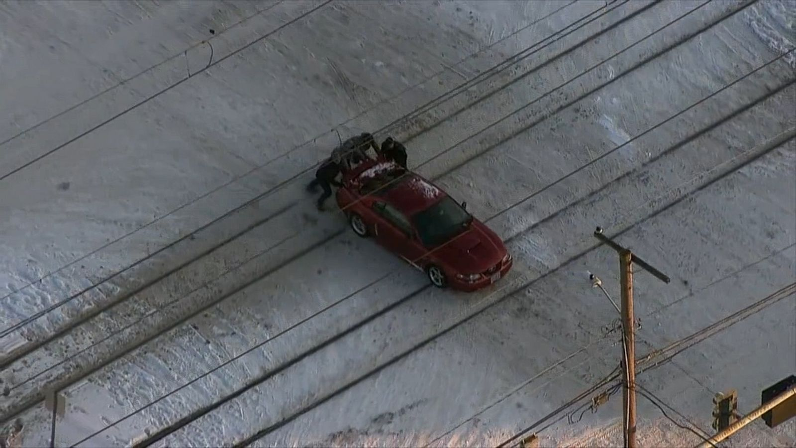 Good Samaritans push a car stuck on the train tracks seconds before a commuter train came barreling through.