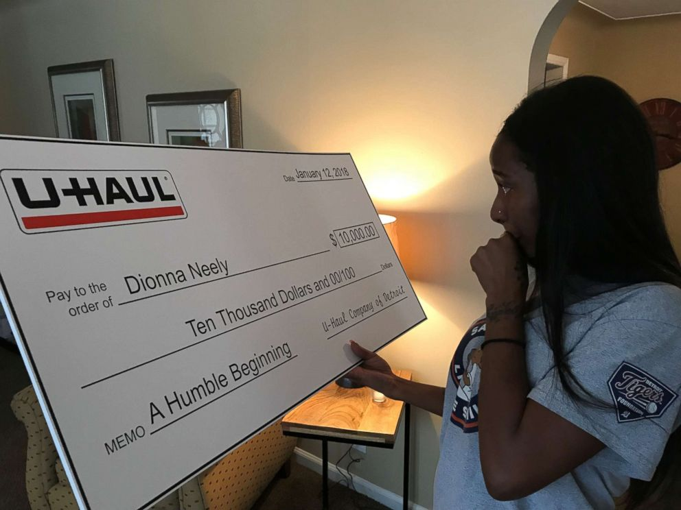 PHOTO: Dionna Neely was presented with a check to help her finish nursing school by the U-Haul Company of Detroit Jan. 12. She said she and son Daerye were incredibly grateful to everyone whod helped their family.