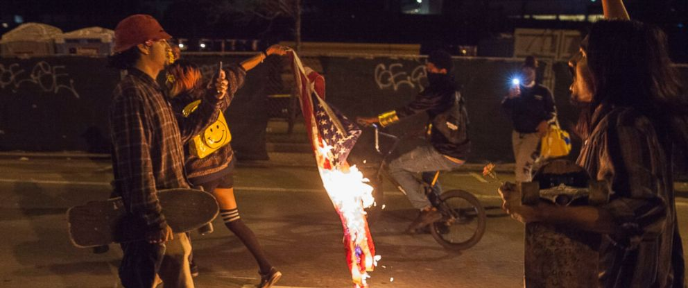 PHOTO: A demonstrator drags a burning American flag through the streets during a march through the streets in protest against President-elect Donald Trump in Oakland, California, Nov. 10, 2016.