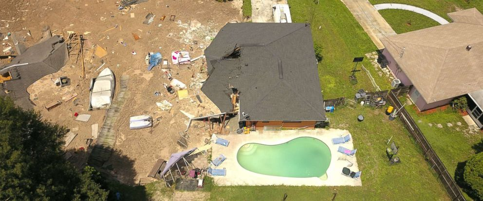 PHOTO: In this aerial photo, debris is strewn about after a sinkhole damaged two homes in Land O Lakes, Fla., July 14, 2017.