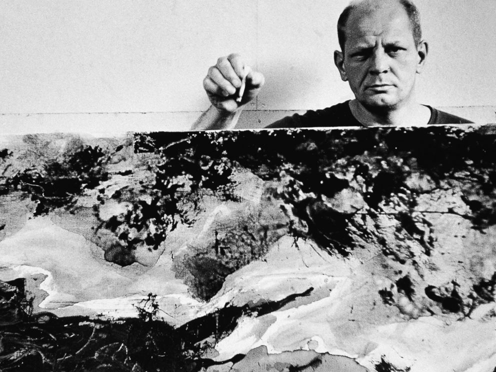 PHOTO: American abstract expressionist painter Jackson Pollock holds a cigarette with one of his paintings in his studio at The Springs, East Hampton, N.Y., Aug. 23, 1953.
