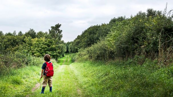 PHOTO: A boy stands in a rural landscape with his backpack in this undated stock photo.