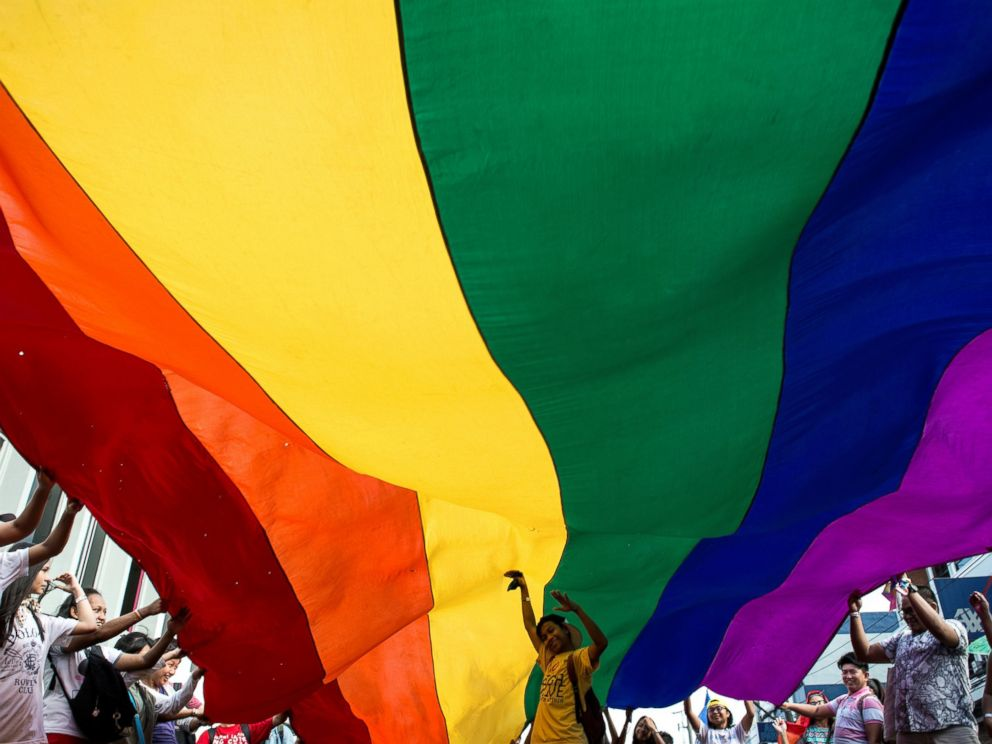 PHOTO: Participants parade the rainbow color flag during a gay pride march in Manila, June 24, 2017. <p itemprop=