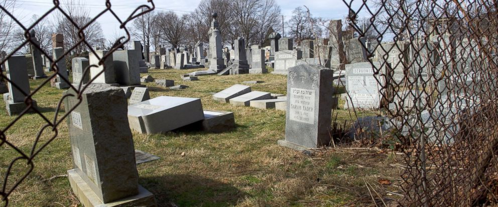 PHOTO: Vandalized Jewish tombstones are framed through a hole in the fence surrounding Mount Carmel Cemetery, Feb. 27, 2017, in Philadelphia, Pennsylvania