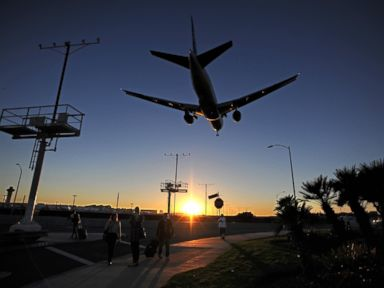 PHOTO: Passengers pull their luggage outside Los Angeles International Airport (LAX) as a plane comes in for a landing at dusk November 1, 2013 in Los Angeles, California.
