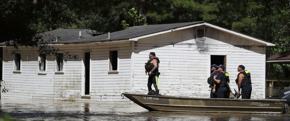 PHOTO: Rescue workers check a neighborhood as flood waters continue to inundate the area, on Aug. 16, 2016, in Port Vincent, Louisiana.